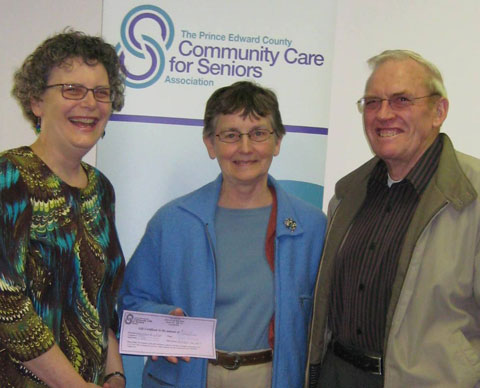 L-R Debbie MacDonald Moynes from Prince Edward Community Care presents contest winners Carrolle and Ken Wright from Consecon with gift certificates to the Seniors Luncheon Social for having submitted the new name chosen for the program.