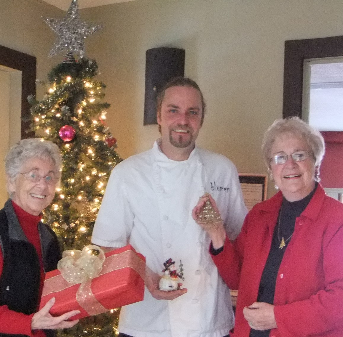 L-R Maureen Finnegan, Andreas Feller, and Edith Morash prepare Community Care's Christmas Memory Tree at Blumen Garden Bistro. second shot