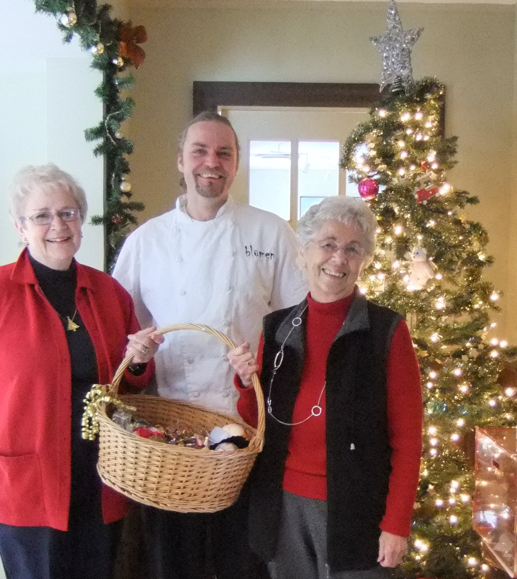 L-R Maureen Finnegan, Andreas Feller, and Edith Morash prepare Community Care's Christmas Memory Tree at Blumen Garden Bistro.