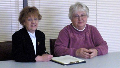 L-R Wendy Davis and Genny Vincent, chairs of the Hospice Prince Edward and Prince Edward Community Care boards of directors, sign a Memorandum of Understanding on January 26, 2006.