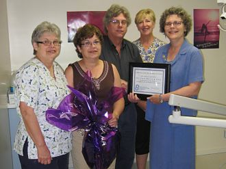 Accepting a gift basket and certificate of appreciation are (L-R) Carol Bigg, Donna Cooper, Dr. Layne Butler, Janice Gordon and making the presentation is Debbie MacDonald Moynes, executive director of Community Care for Seniors.